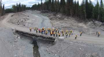 Likely community site tour June 12, 2015 - group stands on Gavin Lake Road bridge to view the channel reconstruction and erosion control work progress. / photo courtesy Imperial Metals
