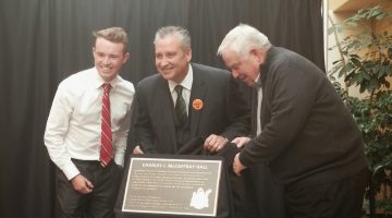 Liam Stewart, McCaffray's grandson, UNBC President Daniel Weeks and Tom Steadman unveil the plaque with McCaffray's name